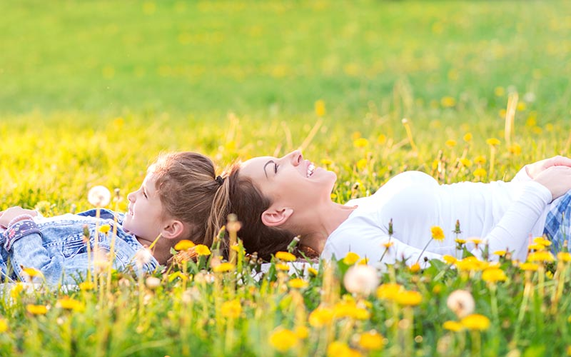 Mother and daughter lying in a dandelion field (extra small)