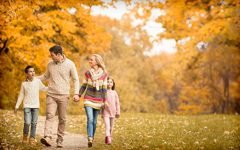 Family of four holding hands and walking outside in Fall setting