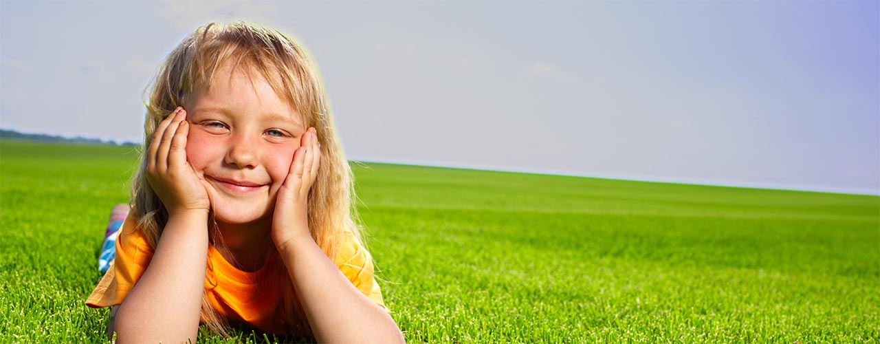 Young girl lying in a fresh-cut, grass field (medium)