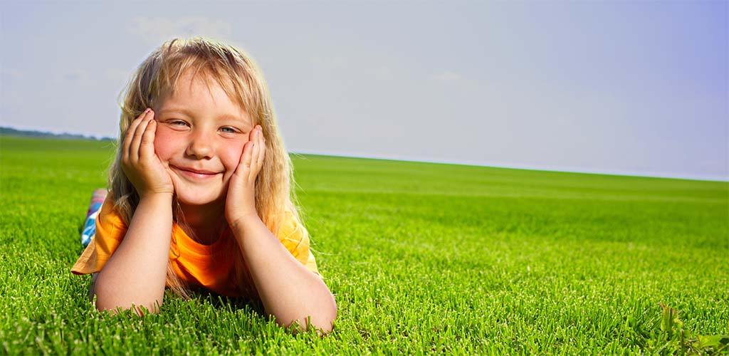 Young girl lying in a fresh-cut, grass field (small)