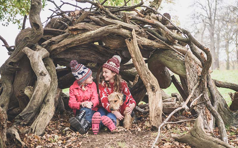 Two girls in a homemade log den during winter