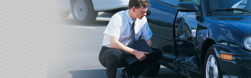 claims adjuster inspecting damage on automobile