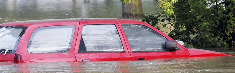red car damaged by flooding waters