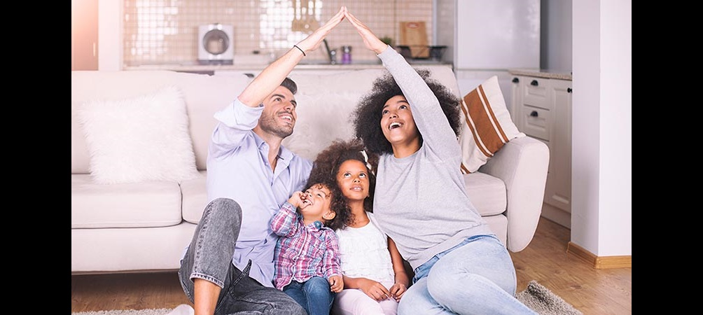 family of four in living room making the shape of a house with their arms