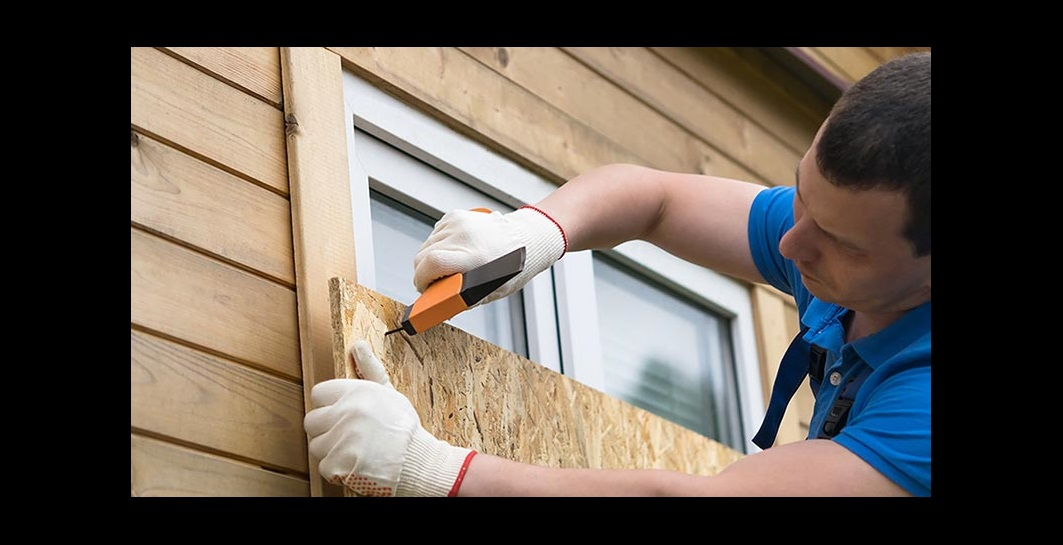 Image of man boarding up a window on a home