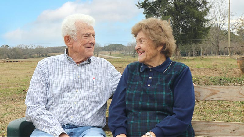 Older couple sitting on a farm bench in a pasture | Alfa Insurance