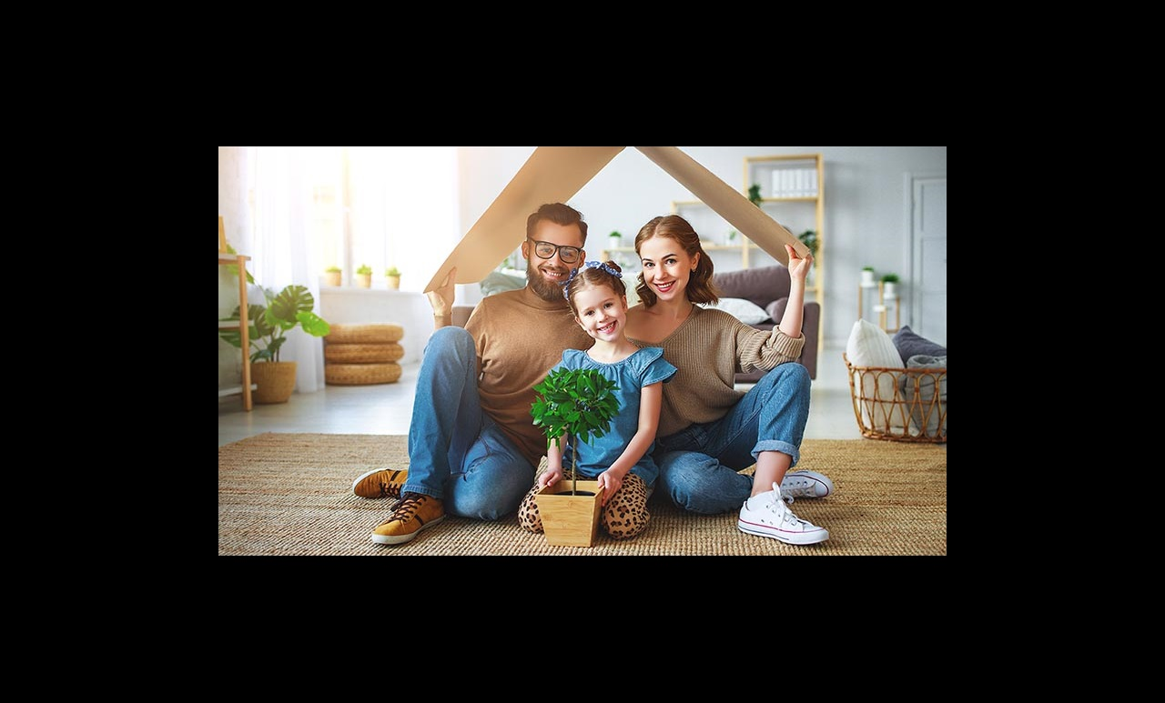 Smiling couple with their daughter holding a cardboard roof over their head
