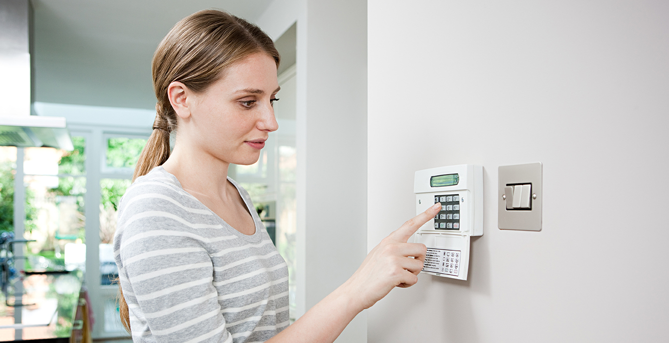 Woman arming home security system to keep home safe while away