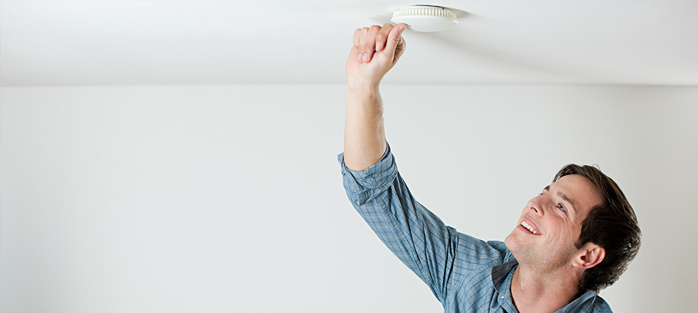 man checking a smoke detector