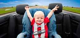 child sitting in car seat with hands in the air