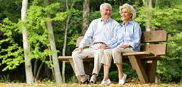 elderly couple sitting on a wooden bench