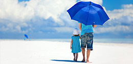 father and daughter walking with umbrella on the beach